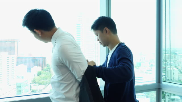 Businessman is dressing his jacket by his assistants video