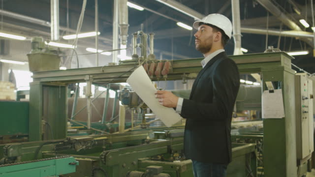 Businessman is looking at projects on a blueprint at an industrial factory. video