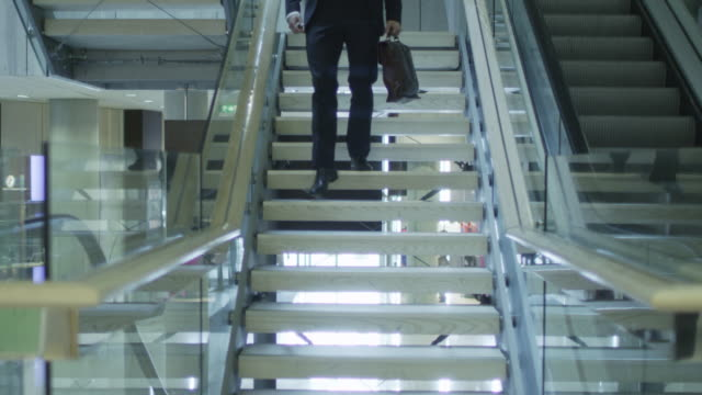 Businessman is Moving Down the Stairs Towards the Camera in Office Building video