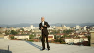 CLOSE UP: Businessman jumping and celebrating the success on rooftop at sunset video