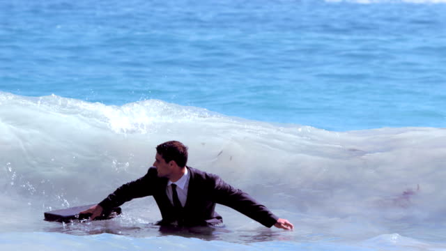 Businessman jumping in the waves video