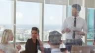 Businessman Leads Meeting Around Table Shot Through Door video