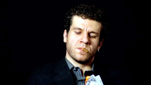 Businessman lights cigar with money video