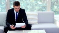 Businessman looking at documents video