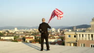 CLOSE UP: Businessman looking proudly down on his hometown holding American flag video
