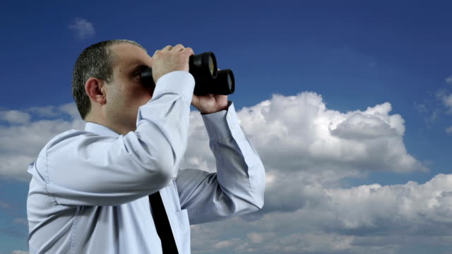 Businessman Looking Through a Binoculars with Moving Clouds video