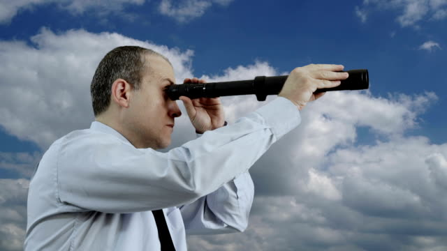 Businessman Looking Through a Hand-Held Telescope with Moving Clouds video