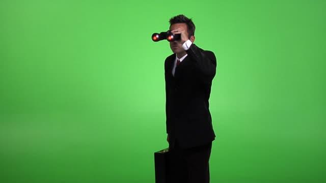 Businessman looking through binoculars video