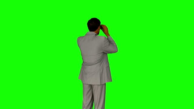 Businessman looking through his binoculars video