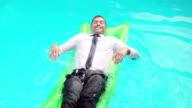 Businessman lying on lilo video