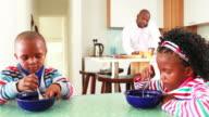 Businessman making breakfast for his children video