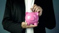 Businessman offering a pink piggy bank video