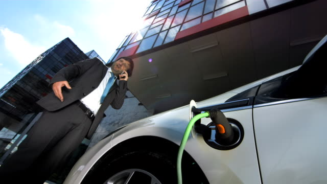 HD: Businessman On The Phone Charging His Car video