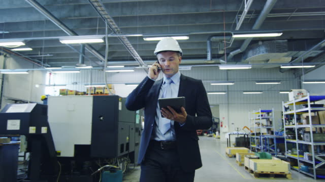Businessman on the Phone Walking through Factory video