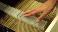 Businessman opens filing cabinet drawer, files folders video