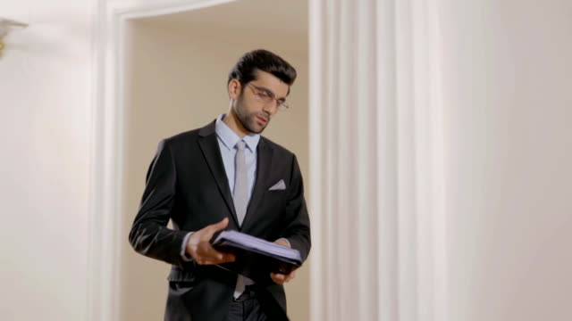 Businessman or lawyer walking with folder in hands over office. opens door. video