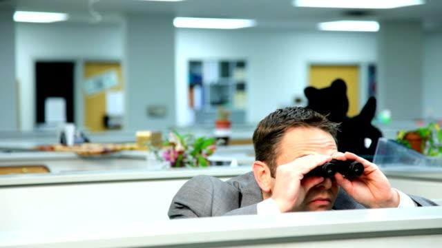 Businessman peeking over cubicle with binoculars video