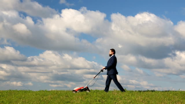 Businessman Pushing a Lawnmower Over Grass video
