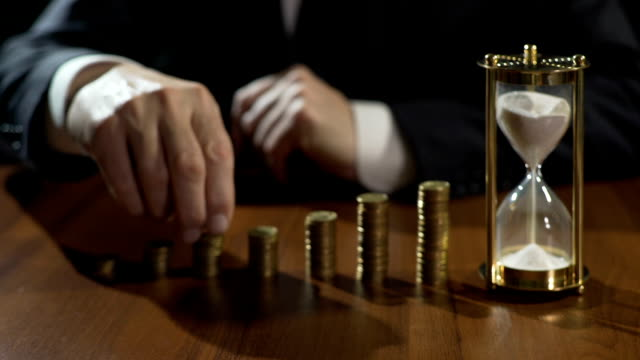 Businessman putting coins on piles, sand flowing in hourglass, deposit interest video