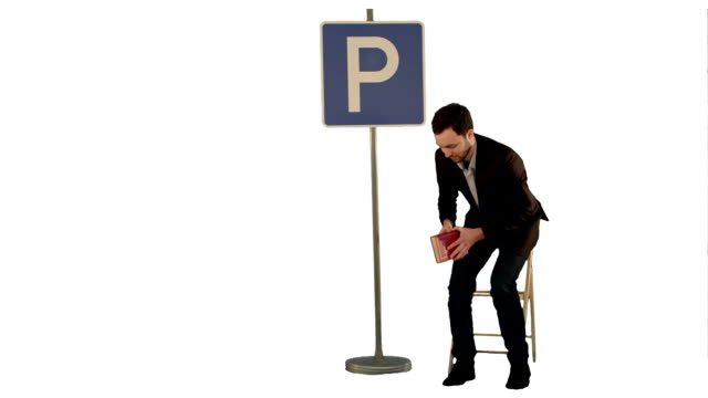 Businessman reading a book near parking sign on white background isolated video