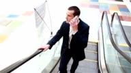Businessman riding on an escalator and talking on the phone video