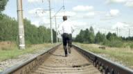 Businessman runs along the rails from camera video