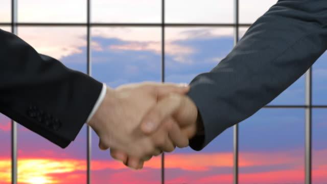 Businessman shake hands at sunset. video