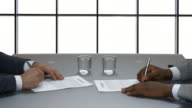Businessman signs a contract on the background of a large window. video