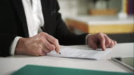 Businessman signs documents video