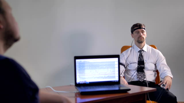 A businessman sits for a lie detector examination. video