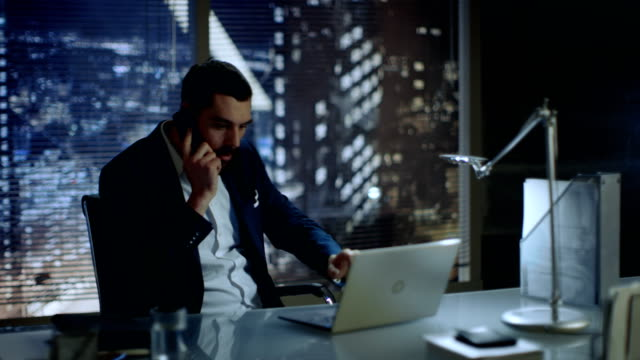 Businessman Sitting at His Desk Talking on the Phone in His Office with Big City View. video