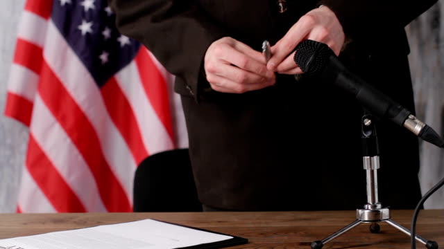 Businessman sitting beside american flag. video