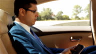 Businessman sitting in the car reading tablet video