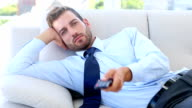 Businessman sitting on couch watching tv video