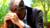 Businessman sitting on park bench with head in hands video