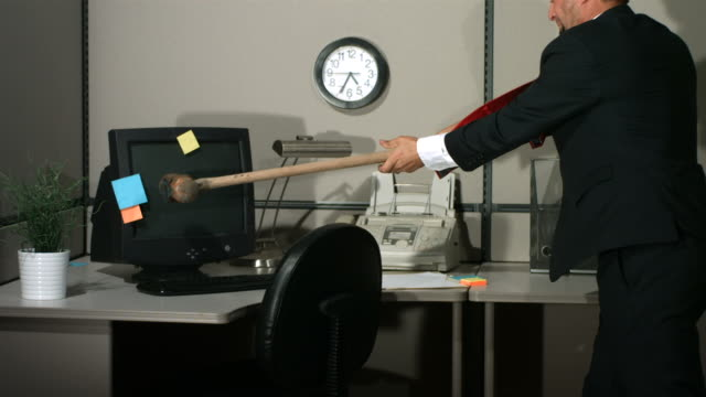 Businessman smashing computer, slow motion video