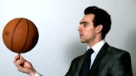 Businessman spinning basketball on finger video