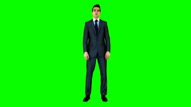 Businessman standing against green background video