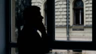 Businessman standing at the window, talking on phone discussing important details. Silhouette video