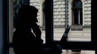 Businessman standing at the window, talking  phone, View information on tablet. Silhouette video