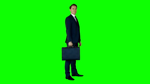 Businessman standing on green screen with suitcase video