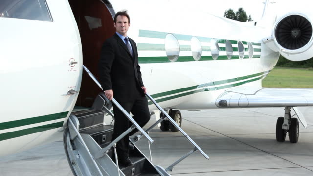 Businessman standing on steps to jet video