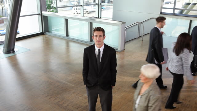 Businessman stands still while others move by video