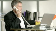 businessman taking care of two phone calls video