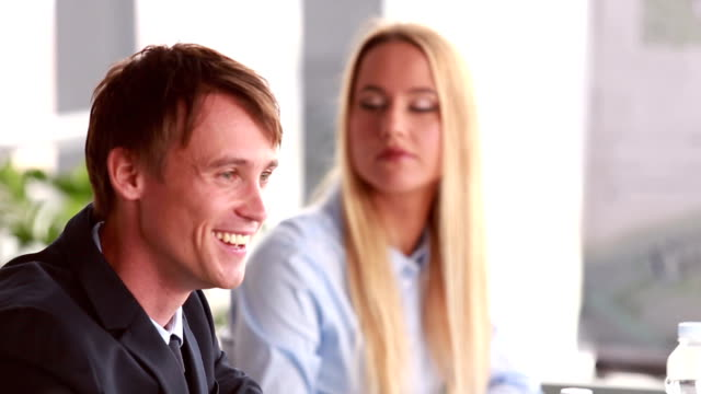 Businessman talking in meeting, female colleague in background video