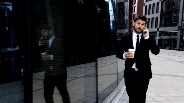 Businessman talking on mobile cell phone in city. Urban male professional drinking coffee video