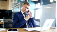 Businessman talking on phone and discussing idea, Multitasking video