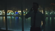 Businessman Talking on Phone by Window at Night video