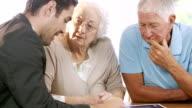 Businessman talking to senior couple video