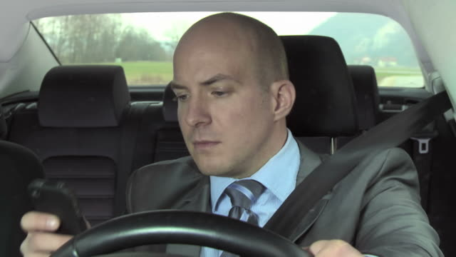 HD: Businessman Text Messaging While Driving video